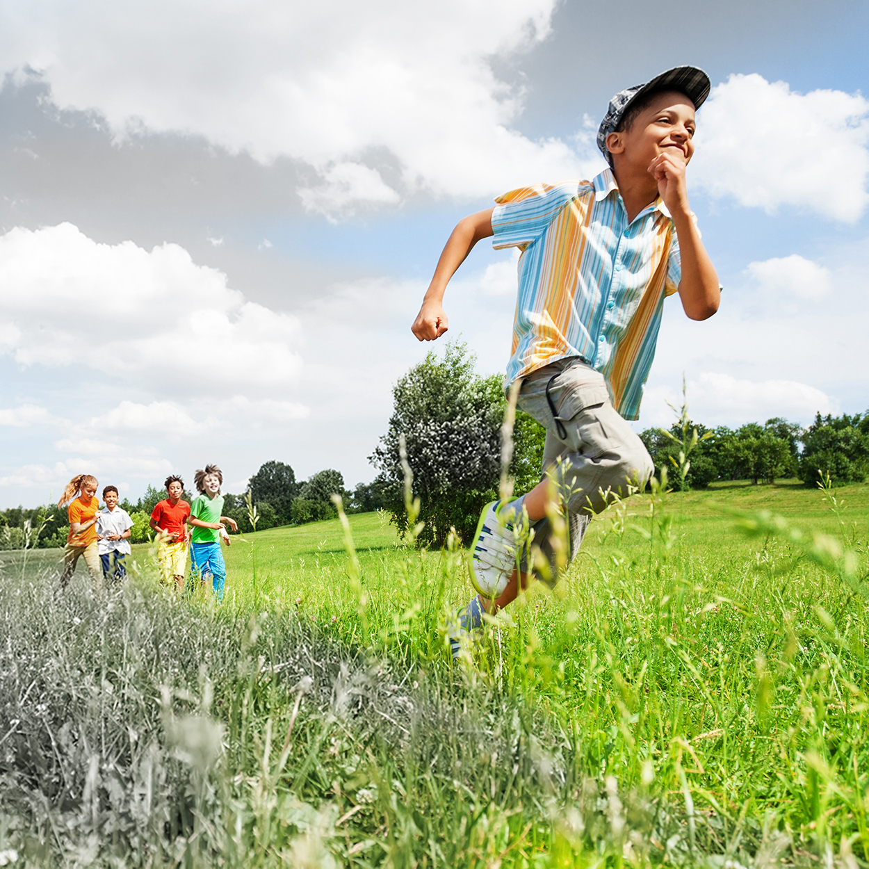 Excited boy runs away from his mates in field